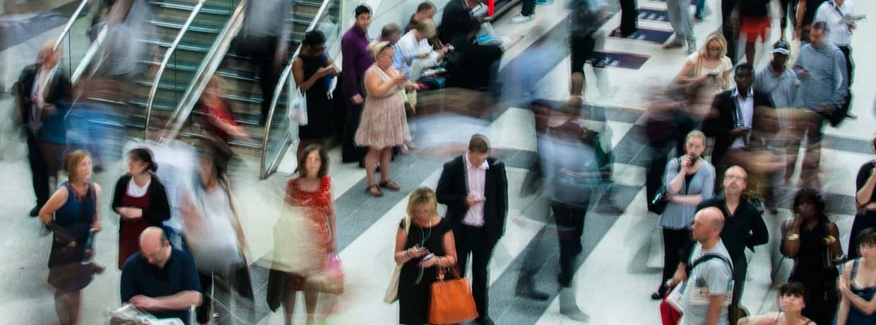 A blur of busy business people consult their smart phone